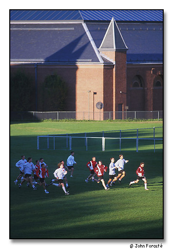 Men's soccer team running sprints in late afternoon light. Andrus Field and the Alumni Athletic Building, Wesleyan University, Middletown, Connecticut. September 2000.