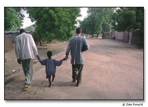 André Doucha, his youngest son and Alex Forasté (Peace Corps Volunteer) visiting as they stroll through their town. <br>Mora, Cameroon, (central west) Africa. August 2002.