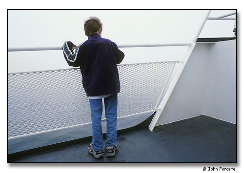 Boy on top deck of the Block Island Ferry on a foggy and windy day. <br> En route from Point Judith to Block Island, Rhode Island Sound/Atlantic Ocean. September 2000.
