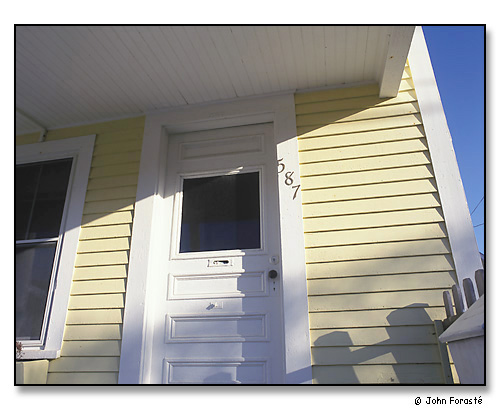 Detail of sunlight, door & yellow clapboards. <br>Provincetown (Cape Cod), Massachusetts. April 2001.